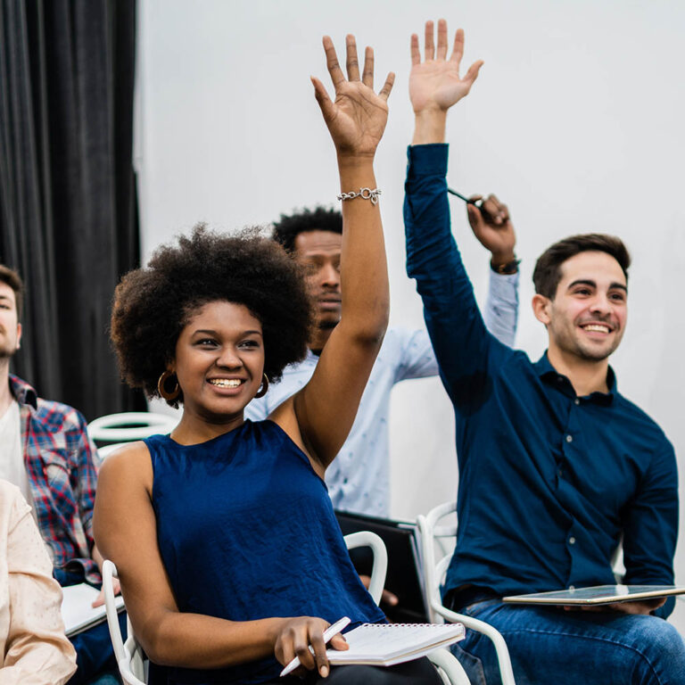 Group of young people sitting on conference together while raising their hands to ask a question. Business team meeting seminar training concept.