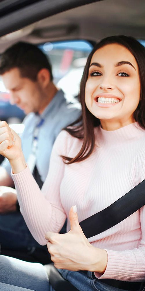 Male auto instructor takes exam in young woman. Happy positive model look on camera with big thumbs up. Smiling with likes. Instructor sit beside her. Passing exams. Daylight outside